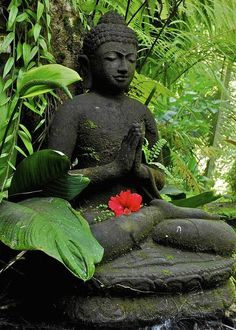 Buddha figure in front of green plants, Ubud, Bali, Indonesia, Asia
