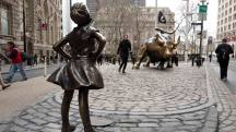 "A statue titled ""Fearless Girl"" faces the Wall Street bull, Wednesday, March 8, 2017, in New York. A big investment firm, State Street Global Advisors, put the statue there to highlight International Women's Day. The work by artist Kristen Visbal. (AP Photo/Mark Lennihan) APTOPIX Fearless Girl Wall Street"